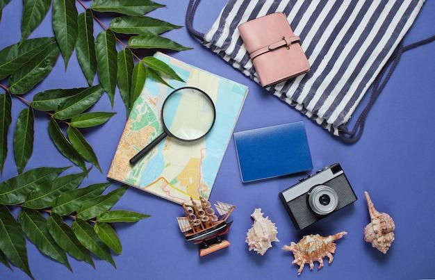 Minimalistyczny płaski styl życia martwej natury. akcesoria turystyczne dla podróżujących na niebieskim tle z tropikalnymi liśćmi