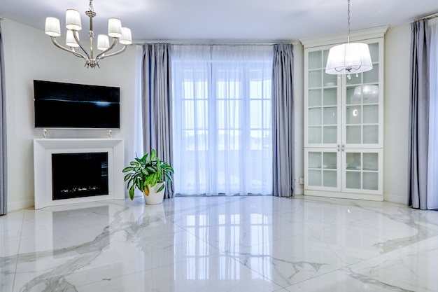 Minimalistyczny pokój dzienny w jasnej tonacji z marmurowymi podłogami, dużymi oknami i kominkiem pod telewizorem