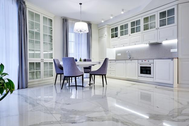 Minimalistyczny pokój dzienny w jasnym tonie z marmurową podłogą, dużymi oknami i stołem dla czterech osób