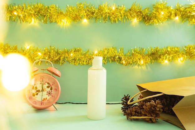 Minimalistyczny pomysł na koncepcję wyświetlania produktów. butelki kosmetyczne na tle bożego narodzenia i nowego roku. budzik. sosnowy kwiat