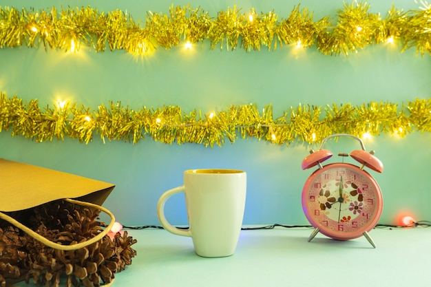 Minimalistyczny pomysł na koncepcję wyświetlania produktów. kubek kawy na tle bożego narodzenia i nowego roku. budzik. sosnowy kwiat