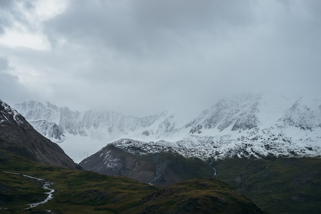 Minimalistyczny, ponury krajobraz wyżynny z ośnieżonymi wysokimi górami w pochmurną pogodę. ośnieżone pasmo górskie w niskich chmurach. nastrojowy minimalizm z zielonymi górami, białym śniegiem i szarym niebem.