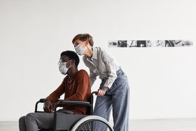 Minimalistyczny portret afroamerykanina poruszającego się na wózku inwalidzkim i oglądającego obrazy w galerii sztuki współczesnej z pomagającą mu młodą kobietą, obie w maskach,