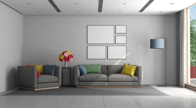 Minimalistyczny salon z szarą sofą i fotelem