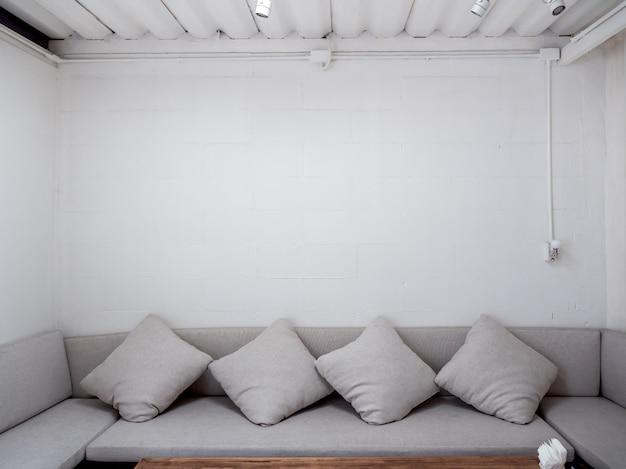 Minimalistyczny salon z szarą sofą z poduszkami na białej ścianie.