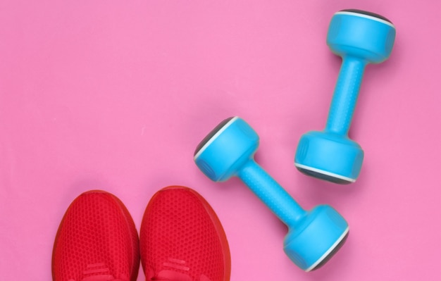 Minimalistyczny sport martwa natura. strój sportowy. czerwone buty sportowe do treningu i niebieskie plastikowe hantle. widok z góry