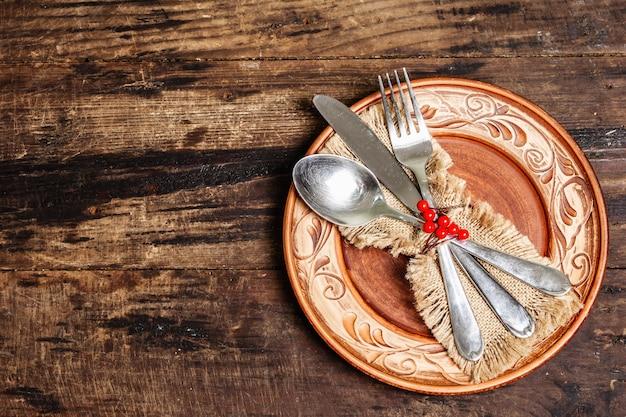 Minimalistyczny stół obiadowy. rustykalny pomysł na święta państwowe ze sztućcami, serwetką worek i świątecznym wystrojem. vintage drewniany stół, widok z góry