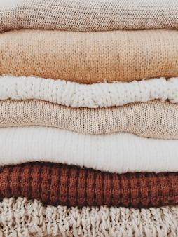 Minimalistyczny stos ciepłych, pięknych kobiecych swetrów lub pulowerów w neutralnych beżowo-brązowych kolorach.