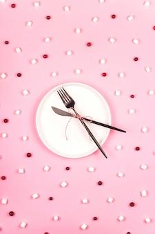 Minimalistyczny świąteczny koncept z białym talerzem na różowo wśród wzoru składników.