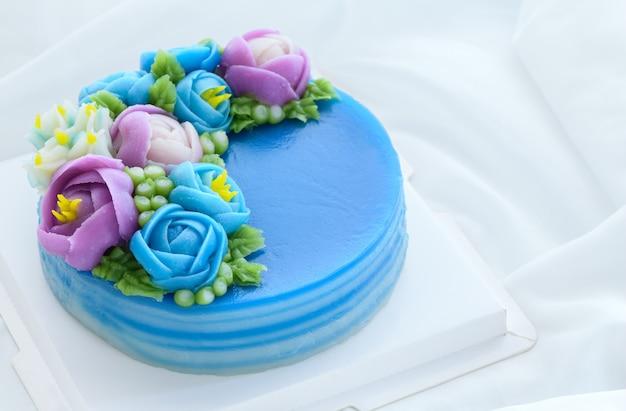Minimalistyczny tort z pandan layer sweet cake i ozdobiony słodkimi kwiatami na białym obrusie. deser tajski