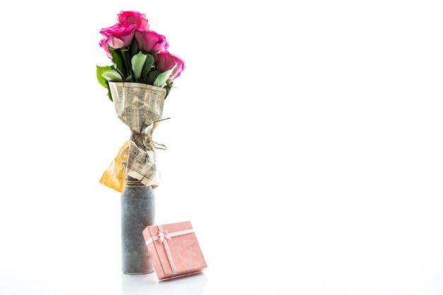 Minimalistyczny wazon z różami i małym prezentem