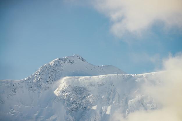 Minimalistyczny widok na ośnieżoną ścianę górską w grubych niskich chmurach w słońcu. malowniczy jasny górski krajobraz z biało-śnieżnym szczytem wśród gęstych chmur na niebieskim niebie. cudowna sceneria ze śnieżną górą.