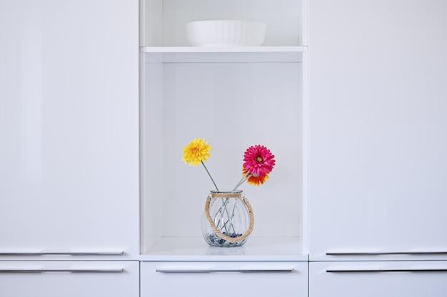 Minimalistyczny wystrój białej kuchni z kolorowymi kwiatami w wazonie
