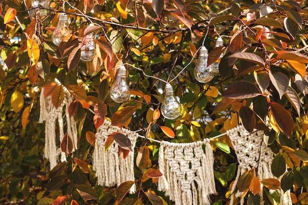 Minimalistyczny wystrój na jesień na żółtym drzewie z żarówkami i girlandą z makramy.