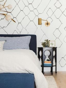 Minimalistyczny wystrój sypialni ze złotą lampą