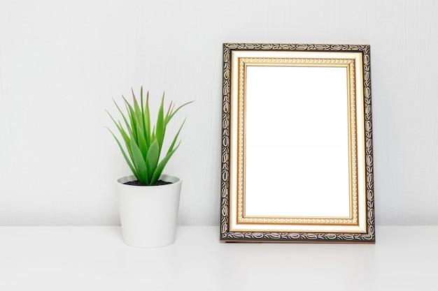 Minimalistyczny wystrój wnętrz z ramą fotograficzną i rośliną w białym garnku na biurku