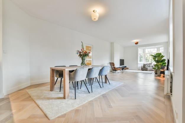 Minimalistyczny wystrój wnętrza nowoczesnego przestronnego, jasnego apartamentu ze strefą jadalną wyposażoną w drewniany stół i wygodne krzesła ustawione na dywanie