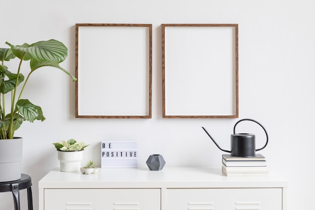 Minimalistyczny wystrój wnętrza z dwiema brązowymi drewnianymi ramkami na zdjęcia na białej półce z książkami, piękną rośliną w stylowej doniczce i akcesoriami do domu. biała ściana.