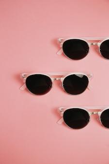 Minimalistyczny wzór pary okularów przeciwsłonecznych na pastelowo różowym tle, projekty i koncepcje letnie