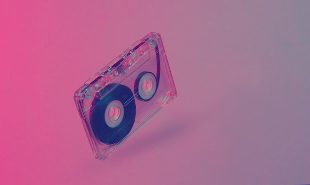 Minimalizm koncepcja w stylu retro. 80s. kaseta magnetofonowa w neonowo-czerwonym, niebieskim świetle. fala retro