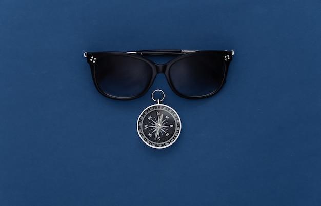 Minimalizm podróży płasko leżał. kompas i okulary przeciwsłoneczne na klasycznym niebieskim tle. widok z góry