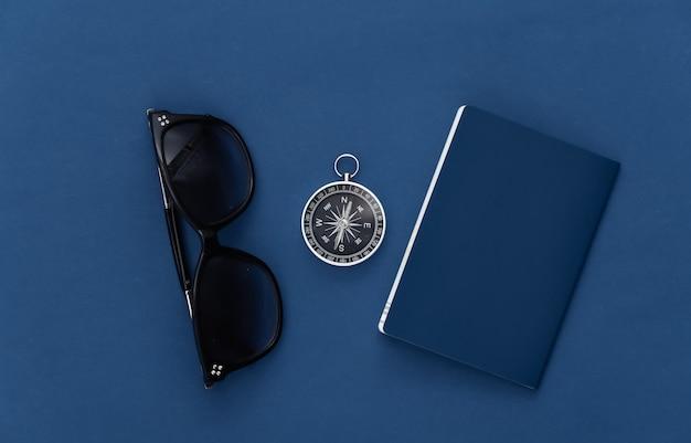 Minimalizm podróży płasko leżał. kompas, paszport i okulary przeciwsłoneczne na klasycznym niebieskim tle. widok z góry