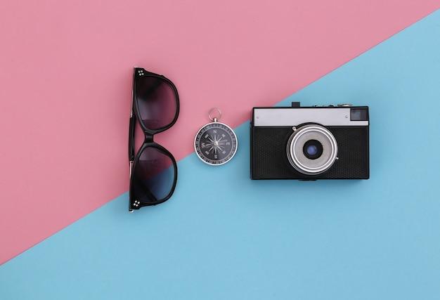 Minimalizm podróży, przygoda na płasko. aparat, okulary przeciwsłoneczne i kompas na niebiesko różowym pastelowym tle. widok z góry