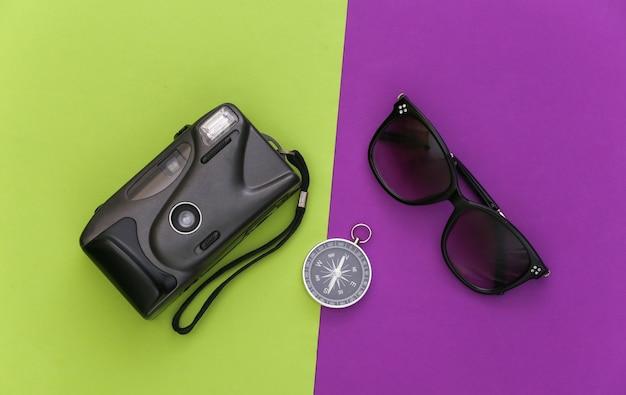 Minimalizm podróży, przygoda na płasko. kompas i aparat, okulary przeciwsłoneczne na fioletowym, zielonym tle. widok z góry