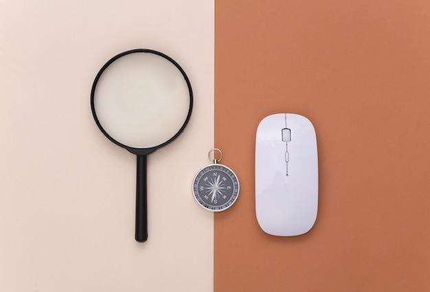 Minimalizm podróży, przygoda na płasko. kompas i lupa, mysz komputerowa na beżowo brązowym tle. widok z góry