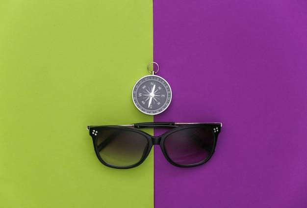 Minimalizm podróży, przygoda na płasko. kompas i okulary przeciwsłoneczne na fioletowym zielonym tle. widok z góry