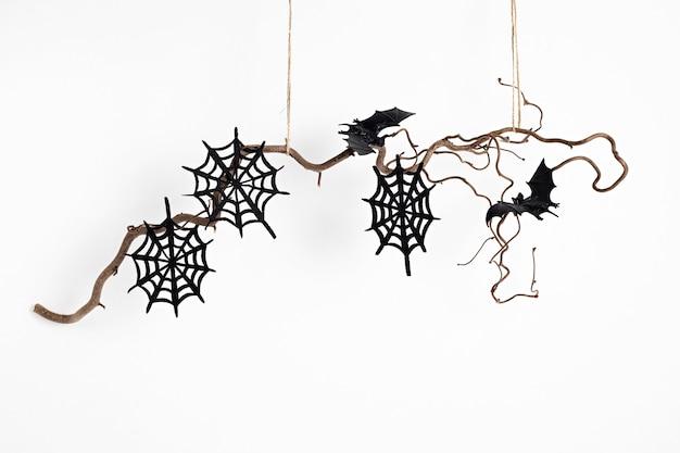 Minimalna dekoracja halloween wisząca na gałęzi drzewa na białym tle