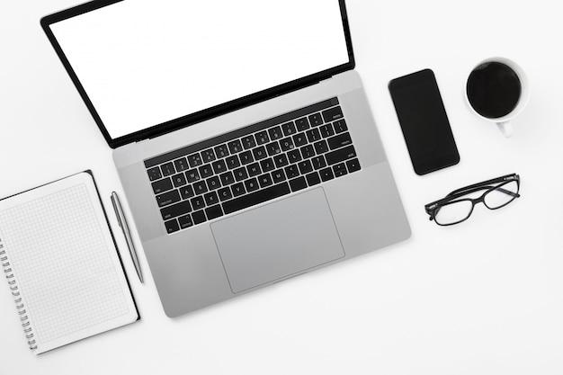 Minimalna freelancer biuro miejsce pracy mieszkanie leżał widok z góry worksplase z laptopem notatnik długopis okulary filiżanka kawy