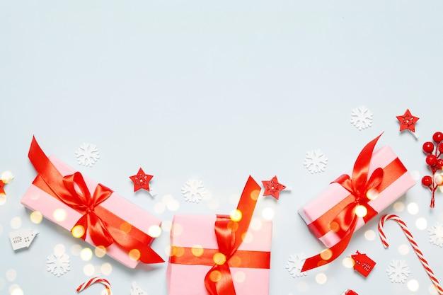 Minimalna kompozycja różowych pudełek z czerwonymi satynowymi wstążkami, świąteczny wystrój