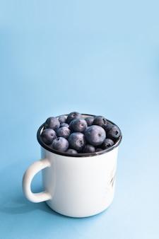 Minimalna kompozycja świeżych jagód w białym metalowym kubku na niebieskim tle.