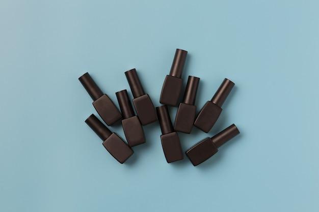 Minimalna kompozycja z czarnymi butelkami lakierów do manicure na niebieskim tle