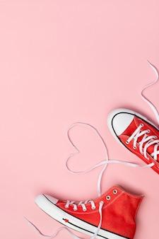 Minimalna kompozycja z czerwonymi trampkami na różowym tle. urodziny dzień matki dzień matki kartkę z życzeniami.