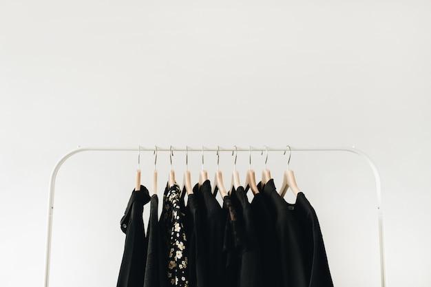 Minimalna koncepcja ubrań moda. czarne bluzki damskie i t-shirty na wieszaku na białym tle.