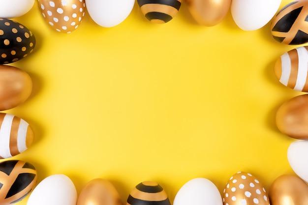 Minimalna koncepcja wielkanocy. złota wielkanocnych jajek rama na żółtym tle.