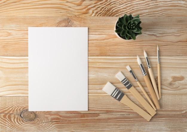 Minimalna makieta artysty ze szczotkami na drewnianym stole i widoku z góry.
