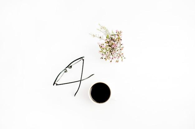 Minimalna płaska kompozycja świecka z okularami, filiżanką kawy i polnymi kwiatami na białym tle