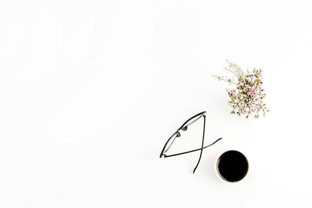 Minimalna, płaska kompozycja, widok z góry z okularami, filiżanką kawy i kwiatami na białym tle