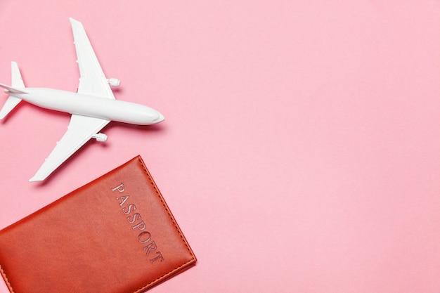 Minimalna prosta koncepcja płaskiej podróży przygoda leżąca z samolotem i paszportem na różowym pastelowym modnym nowoczesnym tle