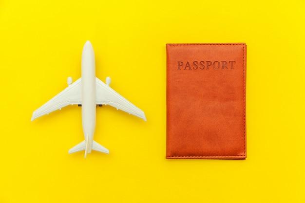 Minimalna prosta płaska podróż przygoda leżała koncepcja podróży samolotem i paszportem na żółtym modnym nowoczesnym tle