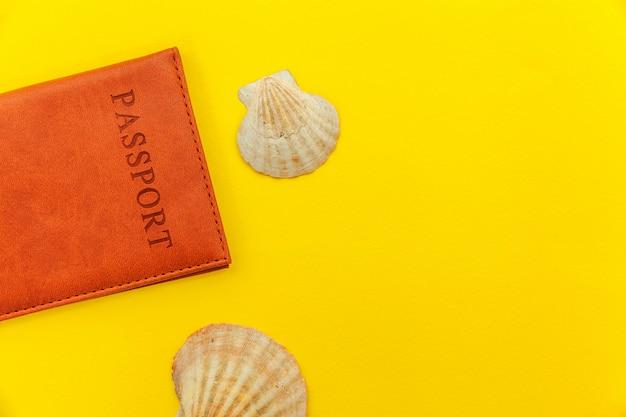 Minimalna prosta płaska podróż przygoda podróż koncepcja podróży z paszportem i muszli na żółtym modnym nowoczesnym tle