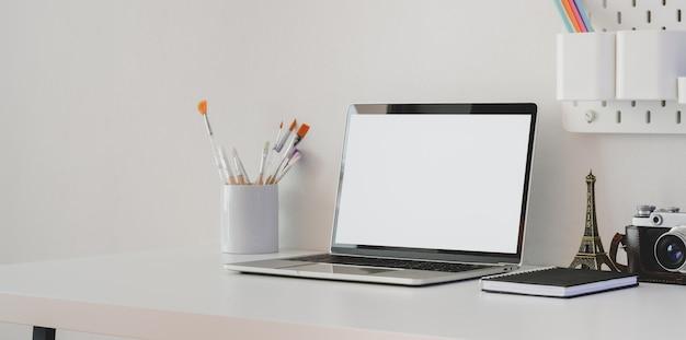 Minimalna przestrzeń robocza artysty z pustym ekranem laptopa z aparatem i dekoracjami