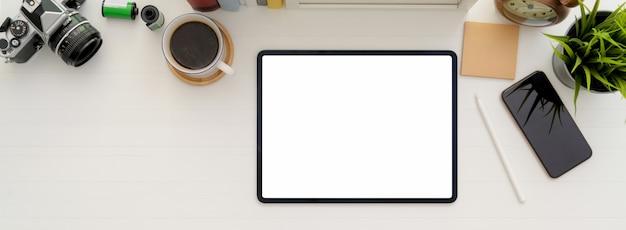 Minimalna przestrzeń robocza dzięki tabletowi z pustym ekranem, filiżance kawy i innym materiałom eksploatacyjnym