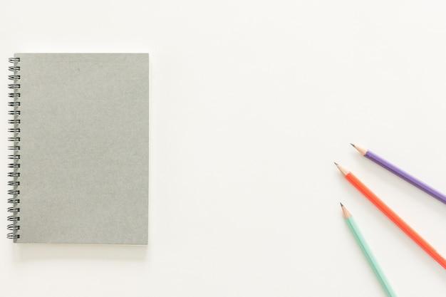 Minimalna przestrzeń robocza - kreatywne płaskie lay zdjęcie pulpitu roboczego biurko z szkicownik i drewniane ołówek na przestrzeni kopii na białym tle. widok z góry, fotografia płaska.
