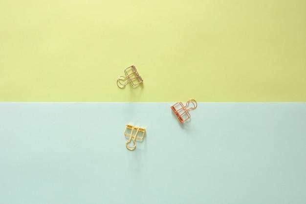 Minimalna przestrzeń robocza - kreatywne płaskie lay zdjęcie pulpitu roboczego z spinacze na kopię pastelowe tło. widok z góry, fotografia płaska.