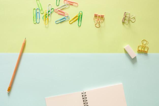 Minimalna przestrzeń robocza - kreatywne płaskie miejsce fotografii pulpitu roboczego biurko z szkicownik i drewniane ołówek na kopię miejsca zielone i niebieskie pastelowe tła. widok z góry, fotografia płaska.
