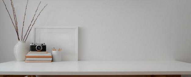 Minimalna przestrzeń robocza z aparatem, książkami, dekoracjami i miejscem do kopiowania